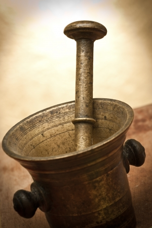 Old bronze mortar and pestle with bay leaves on yellow background