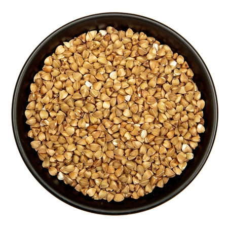 Raw buckwheat in black plate isolated Stock Photo