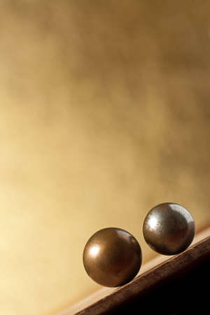 Two vintage metal balls on sloping surface over yellow background  Lot of copy space photo