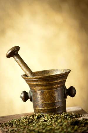 Oude bronzen vijzel en stamper met droge kruiden op gele achtergrond