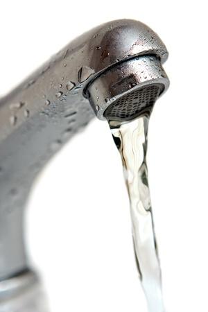 rubinetti: L'acqua che va dal rubinetto isolato su sfondo bianco macro, shallow DOF Archivio Fotografico