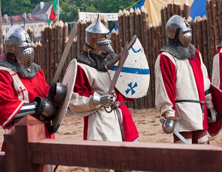 Three medieval knights in red and white waiting for battle photo