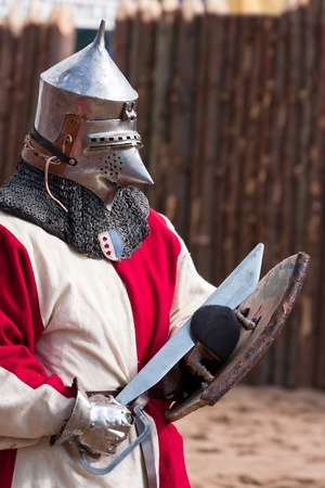 Knight in armour with shield and sword against brown background Stock Photo - 12659708