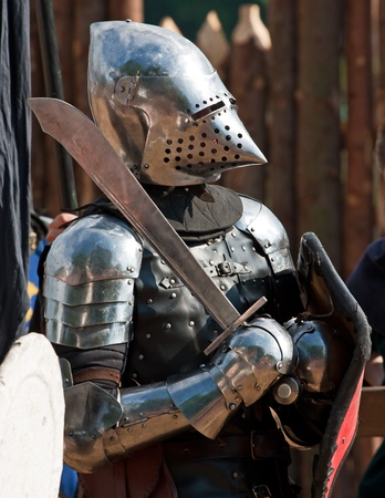 Knight in steel armour with shield and sword against brown background Stock Photo - 12659705