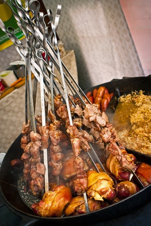Meat pieces on spits in frying pan with roasted pork and sausages photo