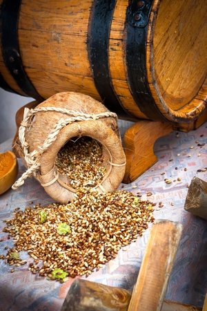 Grains with hop on table by the beer barrel Stock Photo