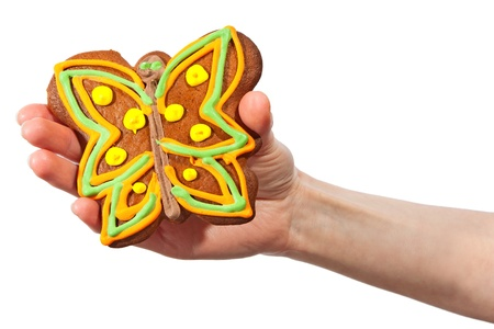 Gingerbread butterfly in hand isolated on white background photo