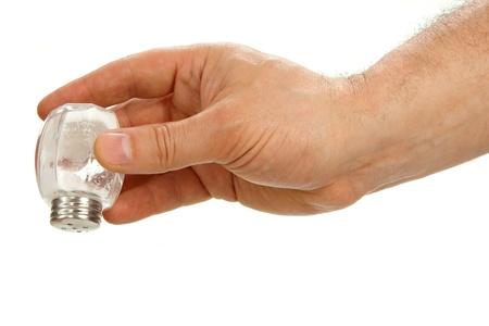 Hand houden zoutvat ondersteboven op een witte achtergrond