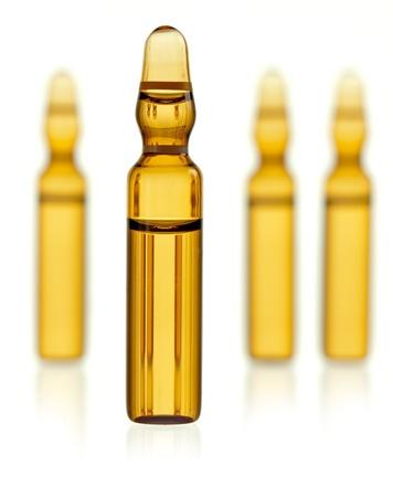 Ampul met geel geneesmiddel met drie ampullen wazig op de achtergrond Stockfoto