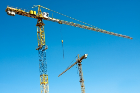 Two construction cranes against clear blue sky Stock Photo - 13731024