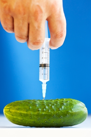 Hand making injection with syringe to cucumber on blue background  GMO concept photo