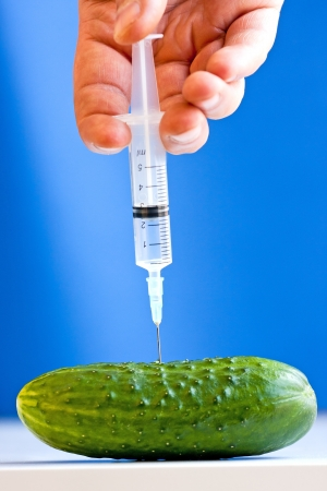 Hand making injection with syringe to cucumber on blue background  GMO concept Stock Photo