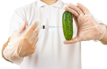 Hands in disposable gloves injecting cucumber with syringe over white background