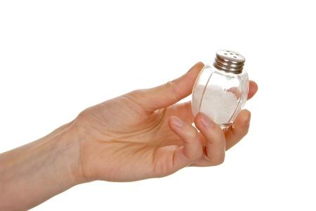 Vrouwelijke hand houden van zout kelder op een witte achtergrond