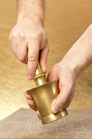 Close up of man hands with mortar and pestle on yellow background photo