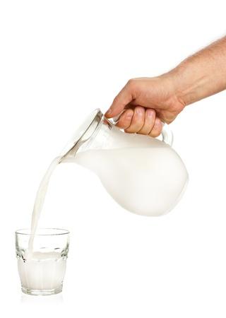 Hand gieten melk van kruik tot glas geà ¯ soleerd op witte achtergrond Stockfoto