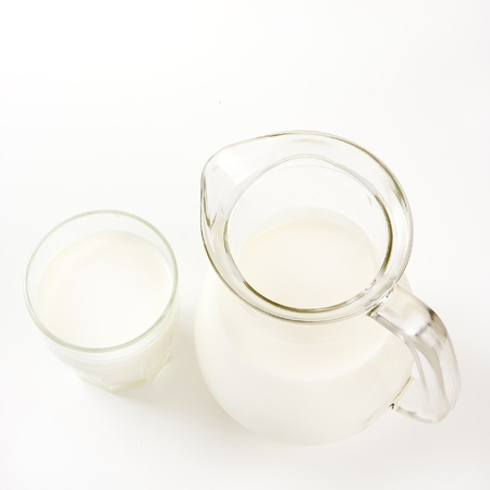 Top view of jug of milk and glass of milk on white