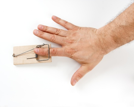 Male finger caught by mouse trap on white background