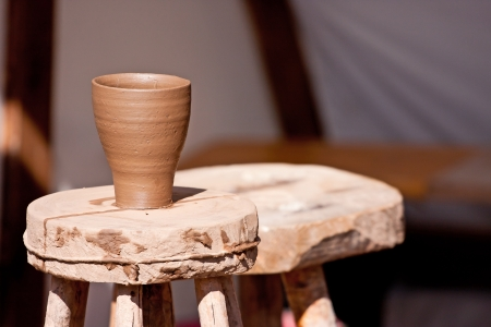 Just made wet clay cup drying on a potter table