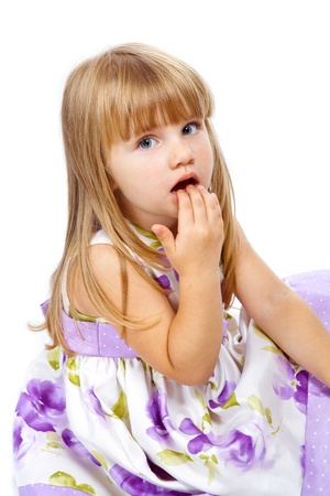 Little beautiful girl putting the fingers in her mouth over white background photo
