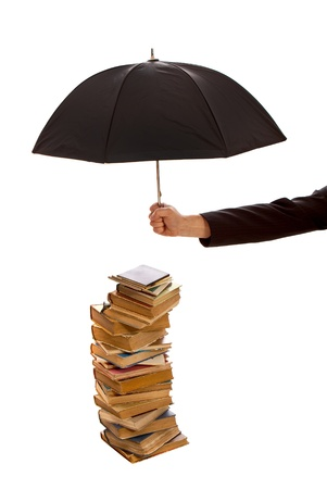 Hand holds black umbrella protecting stack of old books isolated on white Stock Photo - 17043195