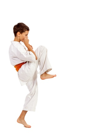 Boy in a kimono practicing martial arts isolated over white background photo