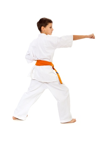Boy in kimono with orange belt making punch isolated over white   photo