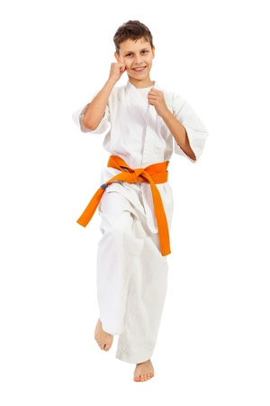 Boy in kimono smiling and making punch isolated over white background photo