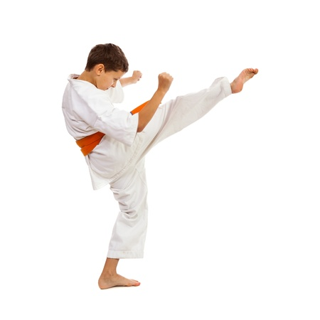 Jonge jongen met kimono en oranje riem, waardoor schop geïsoleerd op witte achtergrond