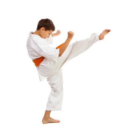 only 1 boy: Young boy with kimono and orange belt making kick isolated on white background Stock Photo