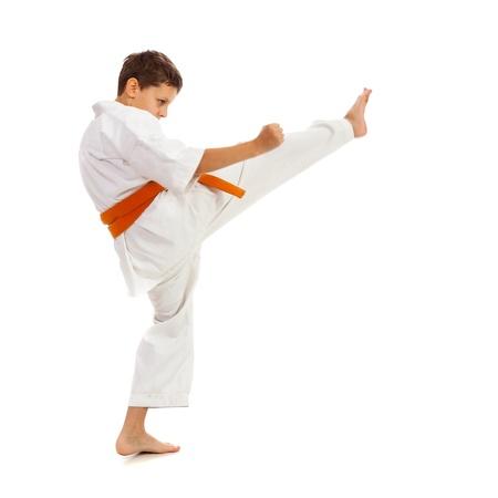 Jonge jongen met kimono en oranje riem, waardoor kick geïsoleerd op witte achtergrond