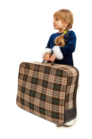 Little girl in blue dress with big old travel suitcase photo