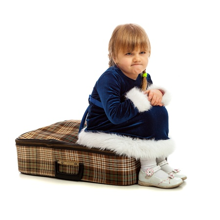 angry child: Little girl sitting angry on big travel suitcase isolated on white