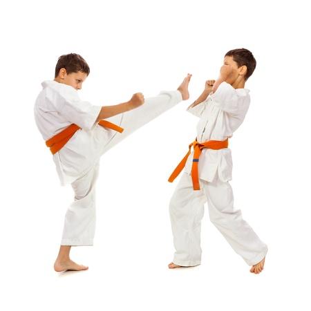 Twee jongens in witte kimono vechten geïsoleerd op witte achtergrond