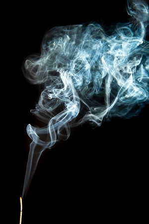 Smoke from incense stick on a black background photo