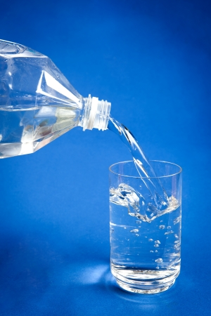 Pouring water from plastic bottle into glass on blue background photo