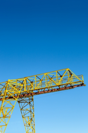 Yellow gantry crane construction over bright blue sky Stock Photo - 19015651