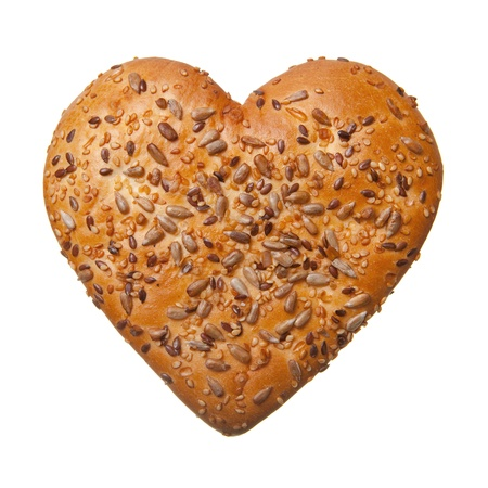 bakery products: Heart shaped bun with sezame and sunflower seeds isolated on white Stock Photo