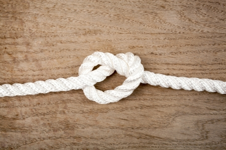 Nylon rope knot on a brown wooden background Stock Photo - 19926340