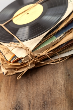 Stack of scratched dusty old vinyl records tied with rope on wooden table  Reklamní fotografie
