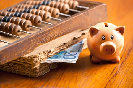 Piggy bank on a table by the old book, counting abacus and 20 euro banknote photo