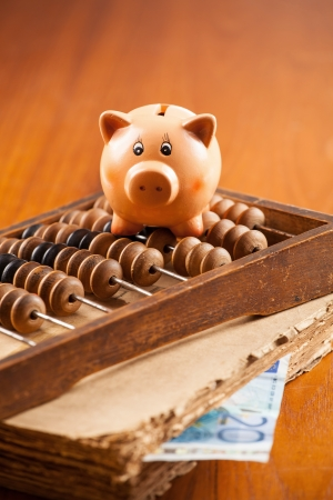 Piggy bank on an old abacus, old book,  and 20 euro banknote photo