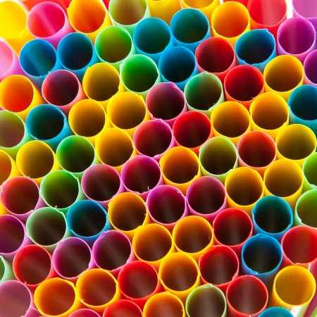 Colored plastic drinking straws holes background. photo