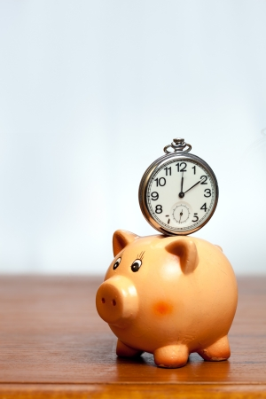 Retro pocket watch on a piggy bank photo