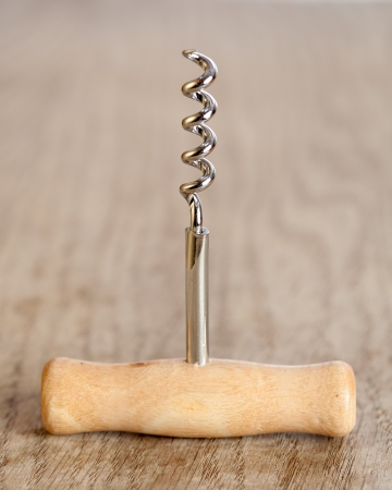 Corkscrew with a wooden handle on a brown table  photo