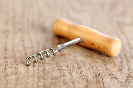 Corkscrew with a wooden handle on a brown table. Selective focus, shallow depth of field photo