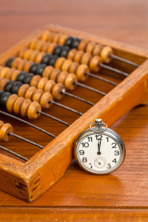 Pocket watch next to wooden abacus on a wooden table photo