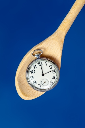 pocket watch on a wooden spoon against blue background photo