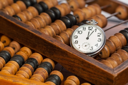 Pocket watch on wooden abacus on a wooden table photo