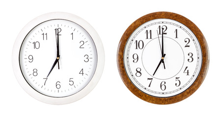seven o'clock: Two clock faces showing seven oclock isolated on white